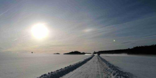 Zasněžená krajina s cestou a pomalu zapadajícím sluncem